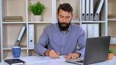 throws up : worker writing something on white paper then throws aside the cameras. handsome journalist or writer is in a state of frustration. bearded man unhappy feels fury and frustration