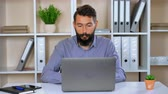 işler : bearded hipster working on laptop in contemporary office. handsome worker with beard and mustache surfing internet or working with project or chatting online sitting at the desk in room with white furniture. friendly employer looking at the camera cheerfu