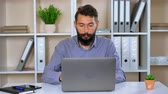 sakallı : adult businessman working in modern office. handsome guy sitting at the workplace typing on laptop. trendy worker wearing casual blue shirt works indoors