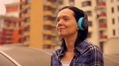 city dweller : positive lady in chequered shirt walks along the street. girl wears blue headphones. Stock Footage
