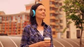 city dweller : woman enjoys morning in weekend time by walking through her neighborhood area. female dweller sips strong coffee in residential quarter. Stock Footage