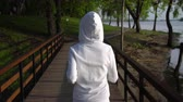 фехтование : woman jogging along the forest lane. girl wears white hoodie.