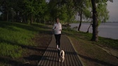 бульдог : young woman fit keep running with french dog in park early morning spring season sunlight. happy girl jogging with pet slow motion