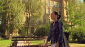 young brunette woman walking in city. casual girl wearing casual shirt enjoy stroll autumn season Stock Footage