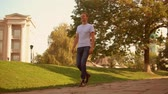 caucasian young man walking in city park. happy guy wearing casual t-shirt and jeans stroll slow motion Stock Footage