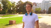 handsome caucasian guy walking in city park. student with headphones wearing white t-shirt strolling slow motion Stock Footage