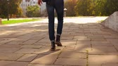 back view young man walking with backpack on the street using talking by phone. caucasian student with blond hair walks outdoor slow motion