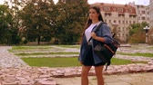 trendy girl with long hair wearing casual shirt and skirt walks outdoors slow motion Stock Footage