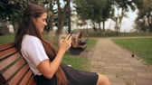 side view cheerful businesswoman with long hair scrolling touch screen mobile sitting on the bench in park