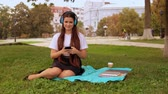 caucasian student sitting on the lawn near tree. young woman listening music in park Filmati Stock