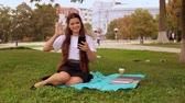 caucasian student has video call sitting on the lawn near tree. young woman use app on mobile for call Stock Footage
