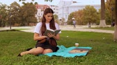 caucasian student reading book sitting on the lawn near tree. young woman with long hair enjoy break outdoors