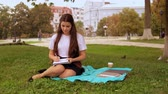 caucasian student writing in notebook sitting on the lawn near tree. young woman with long hair enjoy break outdoors