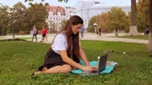 caucasian student typing on laptop sitting on the lawn near tree. young woman with long hair enjoy break outdoors Vídeos