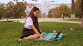 caucasian student has video call with friend sitting on the lawn near tree. young woman with long hair enjoy break outdoors