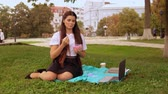 student eating lunch in park. young woman sitting on the grass enjoy break outdoor Stock Footage