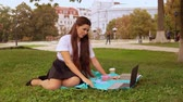 businesswoman relish fruit near tree young woman sitting on the grass enjoy break outdoor Archivo de Video