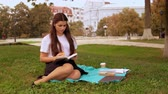 busy student at lunch time young woman holding sandwich reading book Stock Footage