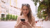 portrait young hipster woman walking using smartphone chatting online or using app for social media or sharing phone. smiling model with dreadlocks wearing trendy sweater slow motion millennial lifestyle Stock Footage
