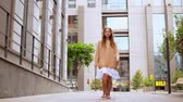 hipster girl with dreadlocks wearing oversized sweater walks on the street downtown area slow motion Stock Footage