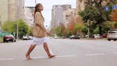 caucasian girl crossing the road windy day slow motion. young woman wearing trendy oversized sweater Stock Footage