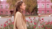 portrait young woman with dreadlocks walking along the road on the background red building Stock Footage