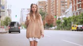 young caucasian woman walking along the road in urban city slow motion. caucasian model with dreadlocks wearing oversized sweater holding cup of coffee drinking on the run outdoors
