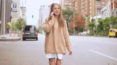 young woman use mobile outdoors walking on the street .smiling caucasian model with dreadlocks wearing oversized sweater going along the road slow motion urban city