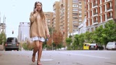 happy hipster woman talking by phone happy smiling during a conversation caucasian model with dreadlocks wearing oversized sweater going along the road slow motion city landscape in autumn season Stock Footage