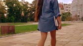 unrecognizable student holding notebook walking on the street. girl with long hair wearing casual shirt and skirt slow motion Filmati Stock