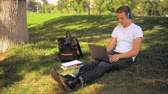 caucasian guy sitting on the lawn in park using laptop. happy student has break listening music Stock Footage