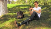 student sitting on the grass using smartphone in park Stock Footage