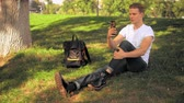 young man sitting in park has video call. caucasian guy using app on smartphone