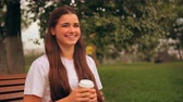 portrait young woman drinking coffee sitting on bench in park looking at the camera and laughing