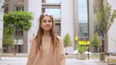 young woman looking at the camera walking in modern urban city. caucasian model with dreadlocks wearing oversized sweater walks on the street downtown area slow motion Filmati Stock