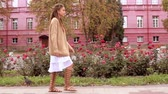 caucasian woman with dreadlocks walking along the road pigeons walk on the grass on the background red building Stock Footage