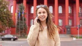 young woman with dreadlocks using smartphone talking by phone with friendly smile goes towards the camera on the background red building slow motion