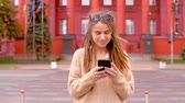 young woman with dreadlocks using smartphone goes towards the camera on the background red building slow motion