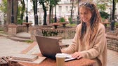 travaux routiers : young caucasian woman with dreadlocks has video call with friend sitting in autumn park. Happy freelancer using webcam on laptop Vidéos Libres De Droits