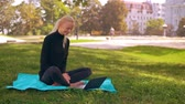 generation z : young caucasian woman with blond long hair using webcam on laptop chatting online sitting on the lawn with green grass. on the background sunny cityscape Stock Footage