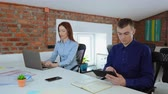 two young employees in startup company sitting at the desk in office with casual interior. redhead businesswoman typing on laptop businessman holding digital tablet Stok Video