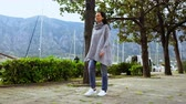 brunette woman walking along the road in city on the background mountain and yachts brunette wearing casual sweater and sneakers walks in mediterranean country spring season.
