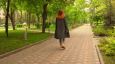 Beautiful Lady Walking Surrounded with Green Trees of Park Road. Girl Going Ahead Turns Head and Smiles. Lifestyle Video
