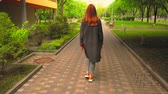 Beautiful Red Haired Woman In Green Park. Walikng Along Path. Wearing Jeans And Black Cardigan. Back View.