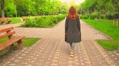 Red-Haired Woman Going by Road Turned Back. Female Wearing Grey Coat Walking in Summer Urban Park. Stockvideo