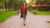 若々しい : Red-Haired Lady Walking in Green Summer Park. Female in Urban Style Going Ahead by Road. Trees on Background. 動画素材