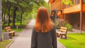 Woman Turned Back Going Ahead. Girl with Red Hair Walking in Summer Park. Helthy Lifestyle.