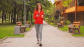 Woman Enjoying Coffee and Looking in Smartphone. Beautiful Lady Walking in Summer Park. Lifestyle Video.
