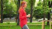 Young Lady Holding Cup and Walking Relaxed. Beautiful Woman Drinking Coffee Outdoors. Lifestyle Video.