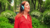 Girl Singing Song in Park. Lady in Headphones Walking on Beautiful Summer Nature. Red-Haired Girl Listens to Music.
